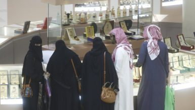 Male and Female shoppers wearing traditional Saudi Arabian dress browse bottles of scent on sale at a luxury concession stand inside the Kingdom Centre shopping mall in Riyadh, Saudi Arabia, on Friday, Dec. 2, 2016. Saudi Arabia is working to reduce the Middle Easts biggest economys reliance on oil, which provides three-quarters of government revenue, as part of a plan for the biggest economic shakeup since the countrys founding. Photographer: Simon Dawson/Bloomberg via Getty Images